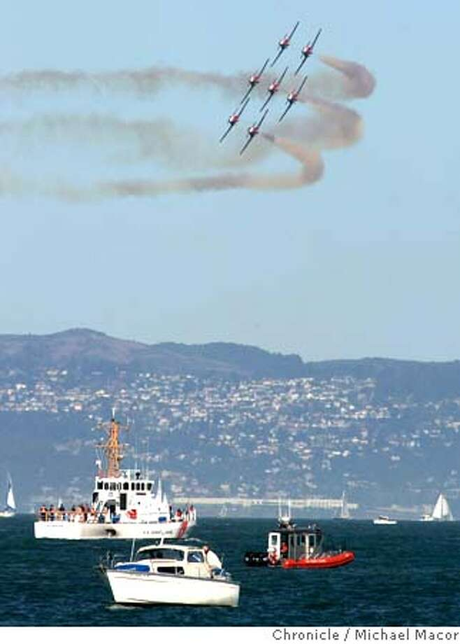 """Canada's, """"Snowbirds"""" percision flying team, soaring low over a group of boats, above San Francisco Bay. keeps in close formation over the Bay. """"Fleetweek"""", officially kicked-off today with a parade of military ships into San Francisco Bay along with an air show featuring the """"Snowbirds"""", Canadian precision flying Team. 10/9/04 San Francisco, CA Michael Macor / San Francisco Chronicle Photo: Michael Macor"""
