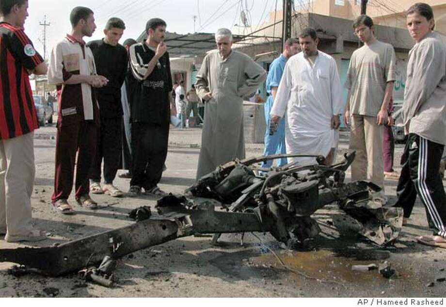 Iraqis gather around the wreckage of a car after a suicide car bomber rammed into a U.S. military humvee in Samarra, Iraq Thursday, March 31, 2005. There were no U.S. casualties, the U.S. military said. Also in Samarra, gunmen briefly attacked a police station with rocket propelled grenades and gunfire, police said.(AP Photo/Hameed Rasheed) Photo: HAMEED RASHEED
