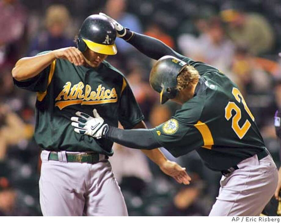 Oakland Athletics' Eric Byrnes, right, steps on home plate and is greeted by teammate Eric Chavez, left, after hitting a two run homer off San Francisco Giants' starting pitcher Kirk Rueter during the 2nd inning of their exhibition game in San Francisco, Thursday March 31, 2005.(AP Photo/Eric Risberg) Photo: ERIC RISBERG