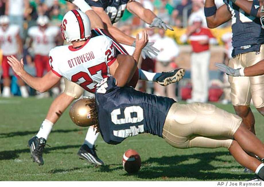 Stanford punter Jay Ottovegio (27) is tackled by Notre Dame linebacker Corey Mays (46) after Ottovegio fumbled a snap during the third quarter Saturday, Oct. 9, 2004, in South Bend, Ind. Notre Dame won 23-15. (AP Photo/Joe Raymond) Photo: JOE RAYMOND