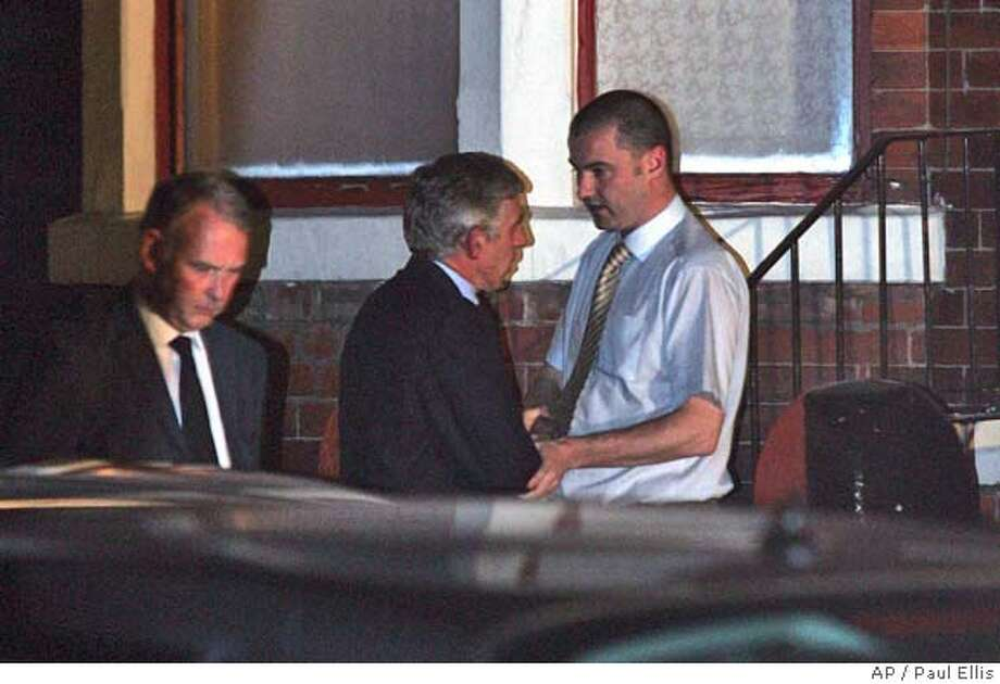 British Foreign Secretary Jack Straw, center, shakes hands with Craig Bigley, right, son of killed British hostage in Iraq Kenneth Bigley, outside the family home in Liverpool, England, late Friday Oct. 8, 2004. The British government exchanged messages with Kenneth Bigley's captors before he was executed in an effort to win his release, Foreign Secretary Jack Straw said Friday. (AP Photo/Paul Ellis) Photo: PAUL ELLIS