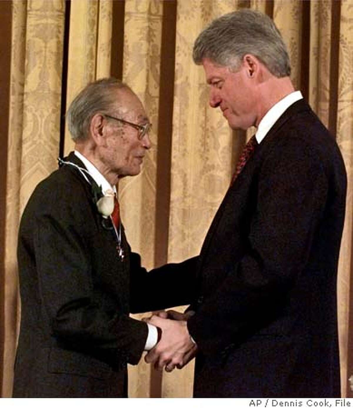 ** FILE ** President Clinton, right, presents Fred Korematsu with a Presidential Medal of Freedom during a ceremony at the White House in Washington in this Jan. 15, 1998 file photo. Korematsu, who unsuccessfully fought the order to be sent to a Japenese American internment camp during World War II, died Wednesday, March 30, 2005. He was 86. Korematsu died of respiratory illness at his daughter's home in Larkspur, said his attorney Dale Minami. (AP Photo/Dennis Cook, file) A JAN. 15, 1998 FILE PHOTO