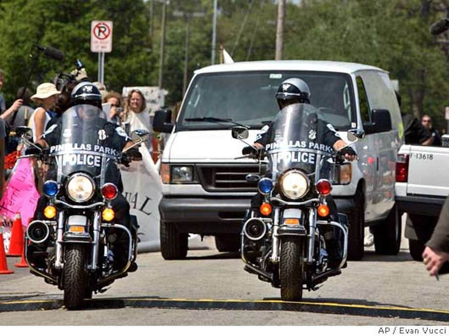 Police escort a van allegedly carrying the body of Terri Schiavo away from the Woodside Hospice on Thursday, March 31, 2005, in Pinellas Park, Fla. (AP Photo/Evan Vucci) Photo: EVAN VUCCI