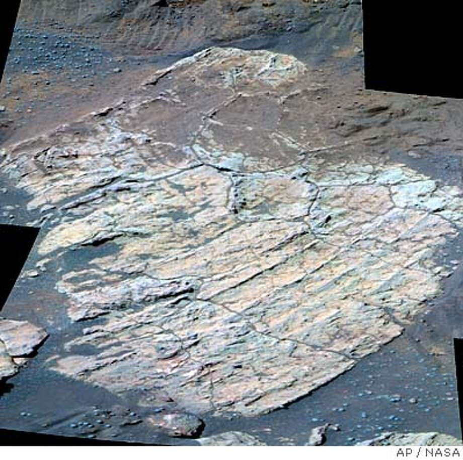 An image taken by the Mars rover Opportunity, shown by NASA during a press conference Thursday, Oct 7, 2004, shows a polygonally fractured rock called Escher, located on the southwestern slope of Endurance Crater. New findings raise the possibility Opportunity's work area was soaked long ago, before it dried and eroded into a wide plain. Evidence of this possibility has been identified in the flat rock Escher and some neighboring rocks near the bottom of the crater. (AP Photo/NASA) Metro#MainNews#Chronicle#10/8/2004#ALL#5star##0422399764