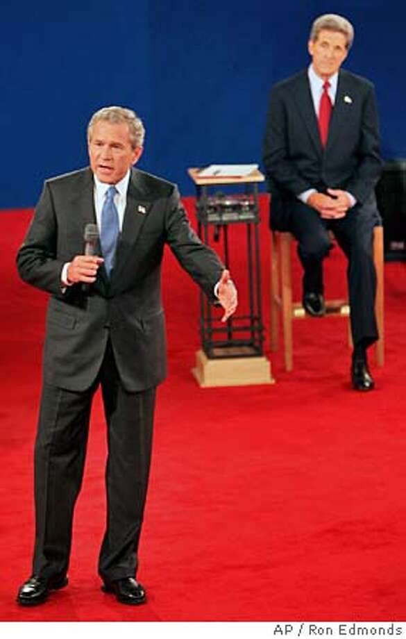 President Bush answers a question during the presidential debate in St. Louis, Friday, Oct. 8, 2004 as Democratic presidential candidate Sen.John Kerry listens. (AP Photo/Ron Edmonds) Photo: RON EDMONDS