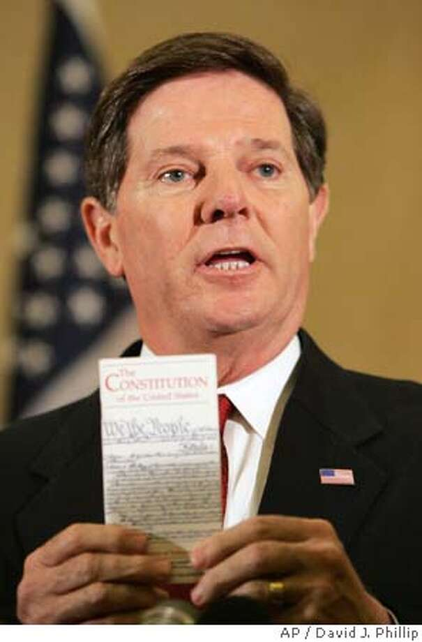 House Majority Leader Tom DeLay, R-Texas, holds a copy of the Constitution of the United States as he speaks about the death of Terri Schiavo Thursday, March 31, 2005 in Houston. Schiavo, the severely brain-damaged woman who spent 15 years connected to a feeding tube in an epic legal and medical battle that went all the way to the White House and Congress, died Thursday, 13 days after the tube was removed. DeLay condemned the judges who at both the state and federal level declined to order that Schiavobe kept alive artificially.(AP Photo/David J. Phillip) Photo: DAVID J. PHILLIP