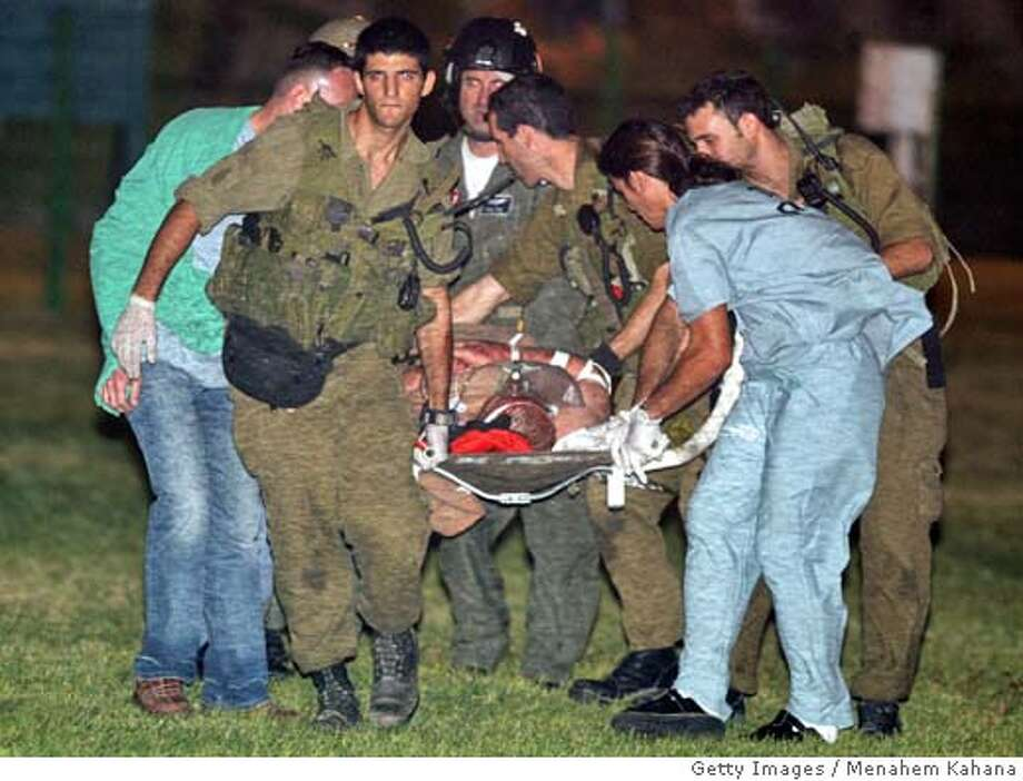A wounded Israeli is carried by Israeli soldiers and medics from a helicopter into a hospital in Beersheva in southern Israel, 08 October 2004. The unidentified man was wounded in a blast that ripped through Hilton hotel in the Red Sea resort of Taba in Egypt's Sinai peninsula late 07 October 2004. The blast was one of three explosions targeting Israelis in Sinai that left at least 30 people dead and scores more wounded. Israeli public television, citing a police source, said a powerful car bomb detonated close to the entrance of the Hilton hotel in the beach resort of Taba just across the border from Israel, destroying a large part of the building. AFP PHOTO/Menahem KAHANA (Photo credit should read MENAHEM KAHANA/AFP/Getty Images) Metro#MainNews#Chronicle#10/8/2004#ALL#5star##0422400545 Photo: MENAHEM KAHANA