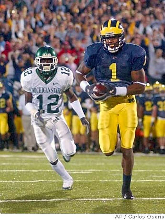 Michigan wide receiver Braylon Edwards (1) outruns Michigan State cornerback Aston Watson (12) for a touchdown during the third overtime period at Michigan Stadium in Ann Arbor, Mich., Saturday, Oct. 30,, 2004. Michigan defeated Michigan State 45-37 in triple overtime. (AP Photo/Carlos Osorio) Ran on: 10-31-2004  Michigan's Braylon Edwards outruns MSU's Ashton Watson for a TD in the third overtime. Ran on: 10-31-2004  Michigan's Braylon Edwards outruns MSU's Ashton Watson for a TD in the third overtime. Ran on: 10-31-2004  Michigan's Braylon Edwards outruns MSU's Ashton Watson for a TD in the third overtime. Photo: CARLOS OSORIO