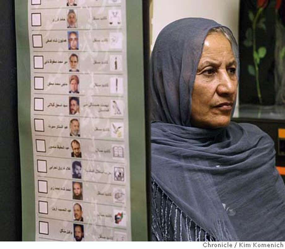 """Bibi Pari of Fremont sits next to a poster listing the candidates in the Afghani election that was brought to the U.S.  Folks in Fremont's """"Little Kabul"""" comment on the upcoming elections in Afghanistan.  Photo by Kim Komenich in Fremont Photo: Kim Komenich"""