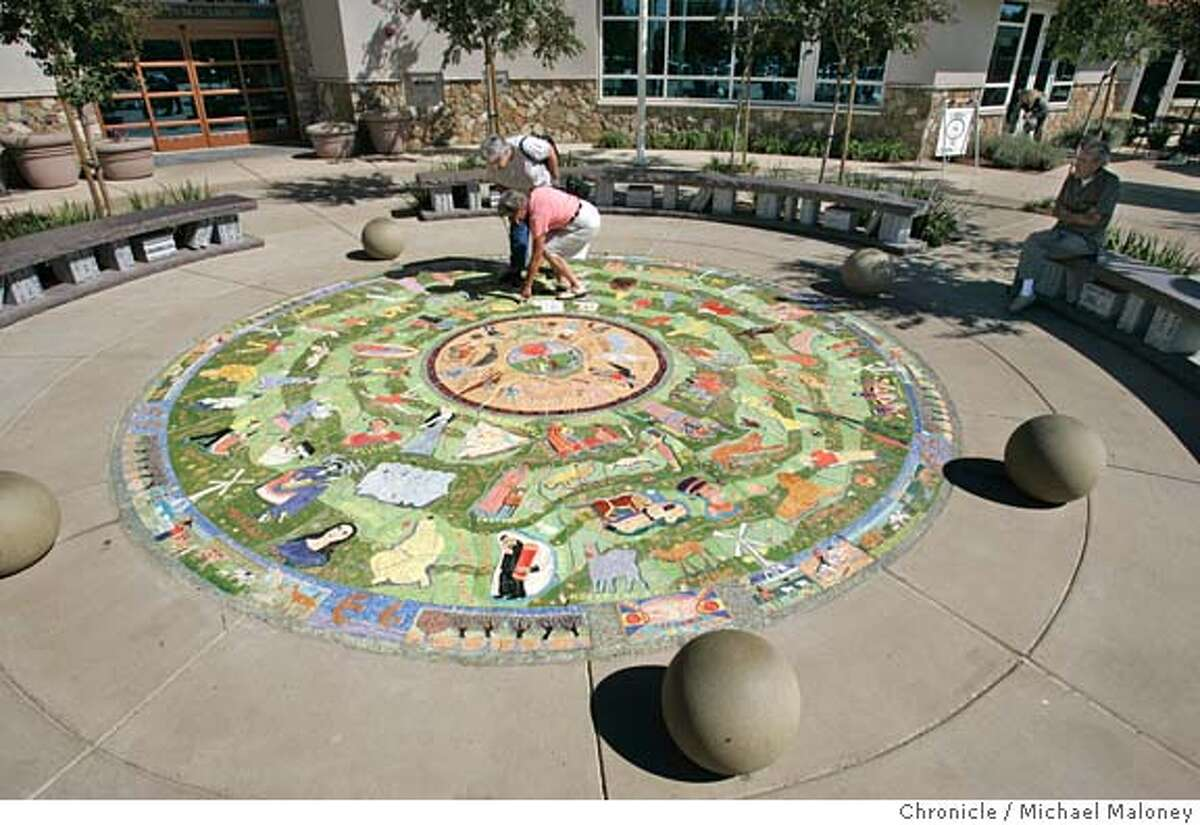 """MURAL003_MJM.jpg Livermore residents Joanne Abey (cq) and Linda Lego look for the misspelled names. Lego's husband Frank lego is seated at far right. A $40,000 ceramic mural unveiled outside Livermore's new library when it opened earlier this year will cost the city $6,000. because of the artist's misspelled names. Einstein, Shakespeare, Vincent Van Gogh, Michelangelo and seven other historical figures were misspelled. """"Our library director is very frustrated that she has this lovely new library and it has all these misspellings in front,"""" said city councilwoman Lorraine Dietrich, one of three council members who voted Monday to authorize paying another $6,000, plus expenses, to fly the artist up from Miami to fix the errors. Artist Maria Alquilar said she was willing to fix the brightly colored 16-foot-wide circular work, but offered no apologizes for the 11 misspellings among the 175 names. """"The importance of this work is that it is supposed to unite people,"""" Alquilar said. """"They are denigrating my work and the purpose of this work."""" Photo by Michael Maloney / San Francisco Chronicle MANDATORY CREDIT FOR PHOTOG AND SF CHRONICLE/ -MAGS OUT Metro#Metro#Chronicle#10/8/2004#ALL#5star#a9#0422400037"""