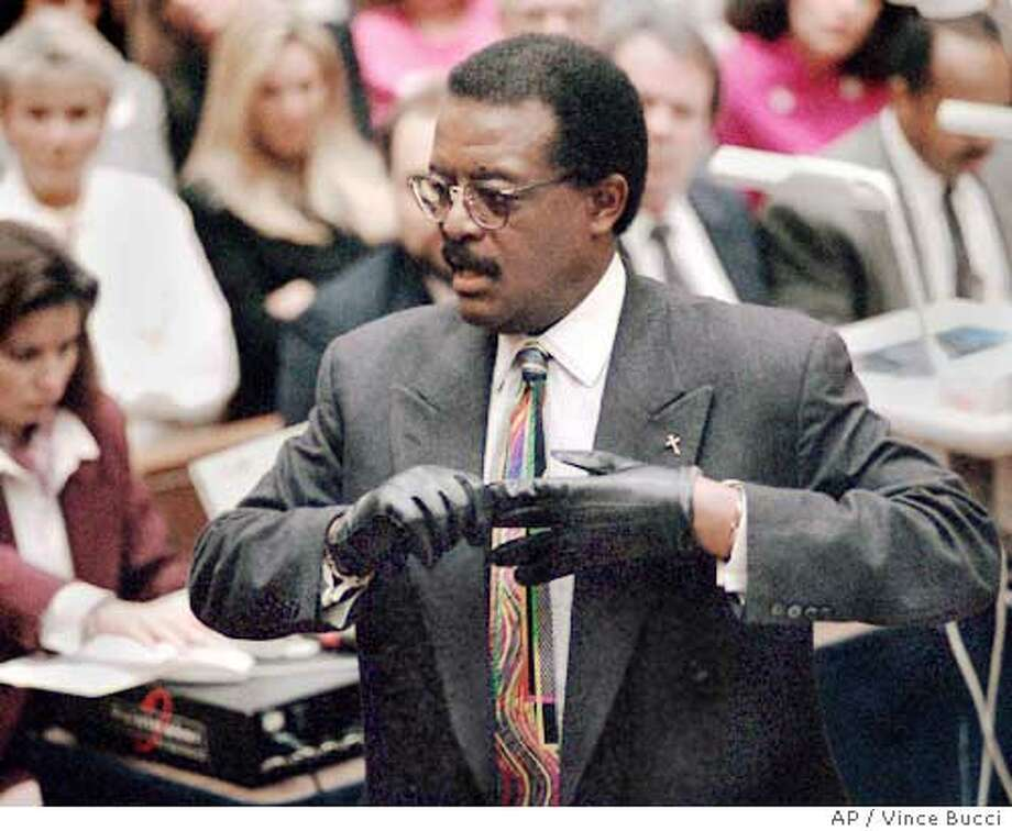 **RETRANSMITTED TO CORRECT OBJECT NAME ** FILE ** Defense attorney Johnnie Cochran Jr. puts on a pair of gloves in this Sept. 27, 1995 file photo, at the Los Angeles Criminal Courts Building, to remind the jury in the O.J. Simpson double-murder trial that the gloves Simpson tried on did not fit him. ``Remember these words,'' Cochran said. ``If it doesn't fit, you must acquit.'' Cochran, the dynamic, eminently quotable attorney whose televised murder defense of Simpson made him a legal superstar died Tuesday. He was 67. Cochran died of a brain disorder in Los Angeles, said law partner Randy McMurray. (AP Photo/Vince Bucci, Pool) Photo: VINCE BUCCI