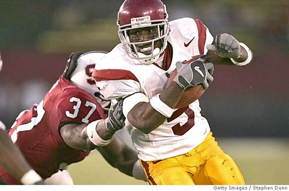 PALO ALTO, CA - SEPTEMBER 25: Running back Reggie Bush #5 of the USC Trojans carries the ball as linebacker Jon Alston #37 of the Stanford Cardinal defends on September 25, 2004 at Stanford Stadium in Palo Alto, California. USC came from behind to win 31-28. (Photo by Stephen Dunn/Getty Images) *** Local Caption *** Reggie Bush; Jon Alston Sports#Sports#Chronicle#10/7/2004#ALL#5star##0422379335 Photo: Stephen Dunn