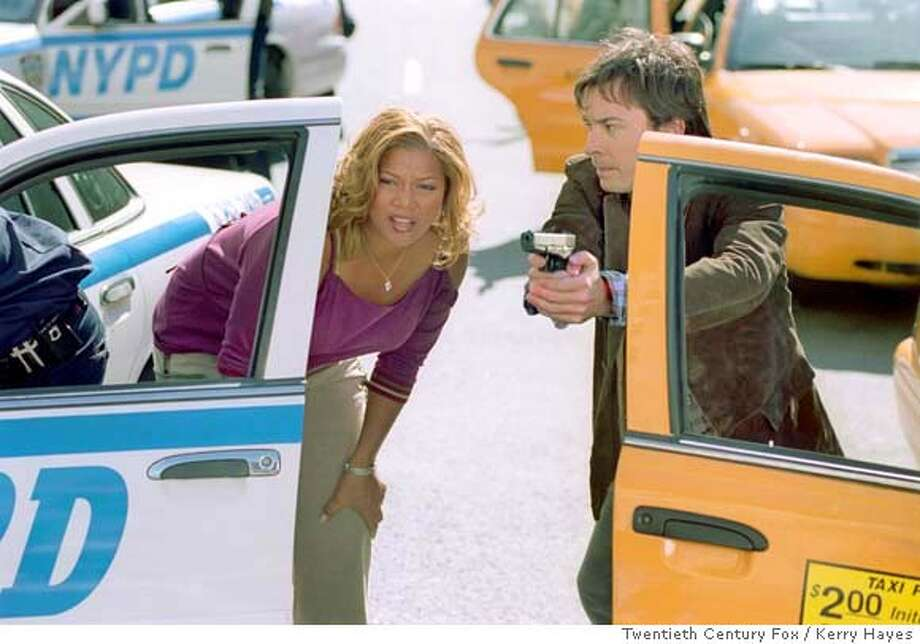TAXI06 Taxi driver Belle (Queen Latifah, left) and undercover cop Washburn (Jimmy Fallon) face off against a gang of seemingly unstoppable bank robbers. Photo Credit: Kerry Hayes/Twentieth Century Fox Datebook#Datebook#Chronicle#10/06/04#ALL#Advance##0422394049