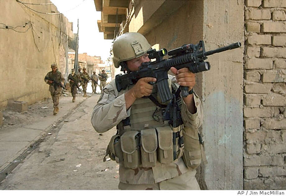 A U.S. Army soldier covers a building as Iraqi National Guard troops patrol an alley in Samarra, Iraq, Tuesday, Oct. 5, 2004, four days after a joint U.S. and Iraqi military incursion into the city. U.S. and Iraqi forces withdrew from the center of the city later Tuesday. (AP Photo/Jim MacMillan) Ran on: 10-06-2004  A GI covers a building as Iraqi national guardsmen patrol an alley in Samarra. Soldiers later withdrew from the center of the city. Photo: JIM MACMILLAN