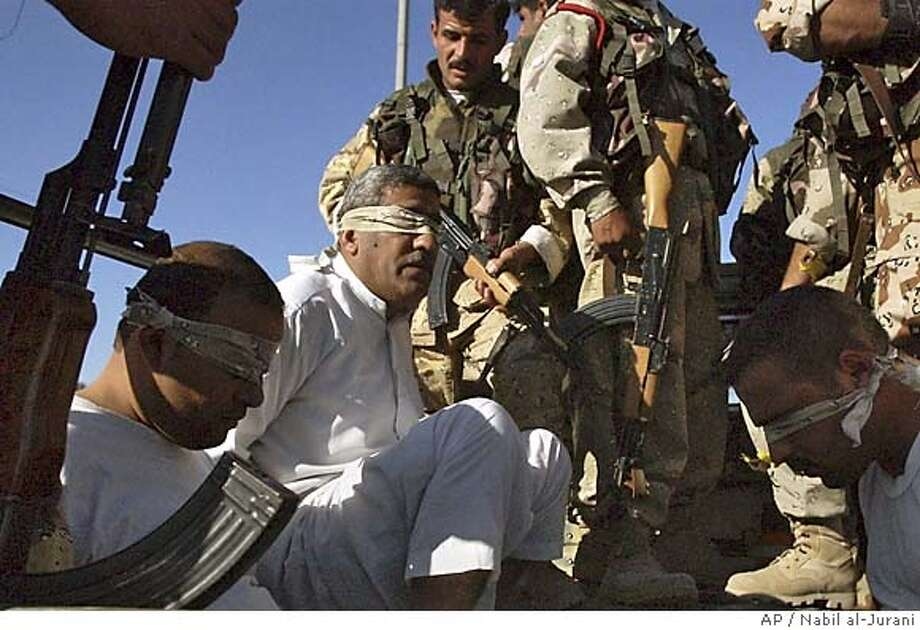 Iraqi Army soldiers detain a group of Iraqi men after a raid on a village near Basra, Iraq Sunday, March 27, 2005. Ten suspected insurgents were detained. Insurgents also hit a Basra police patrol with a roadside bomb Sunday, injuring one nearby civilian, said Lieu. Colonel Karim Ali Al-Zaydi. (AP Photo/Nabil al-Jurani) #######0422739348 Ran on: 03-28-2005  Iraqi army soldiers detain a group of Iraqi men after a raid on a village near Basra. Ten suspected insurgents were detained. Photo: NABIL AL JURANI