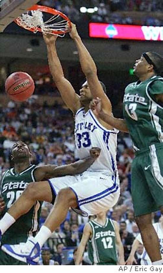 Kentucky's Randolph Morris (33) slams the ball despite the defense of Michigan State's Matt Trannon (20) and Maurice Ager (13) in the second half of the NCAA Austin Region final at the Frank Erwin Center in Austin, Texas Sunday, March 27, 2005. (AP Photo/Eric Gay) Photo: AP / Eric Gay