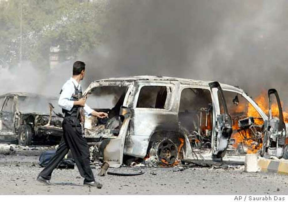 An Iraqi policeman looks at one of the burning four-wheel drives soon after a car bomb ripped through Saadoun street in Baghdad, Iraq, Monday Oct. 4, 2004. The bomb targeted two four-wheel drives carrying foreign nationals and the casualty figure is unknown. (AP Photo/Saurabh Das) Photo: SAURABH DAS