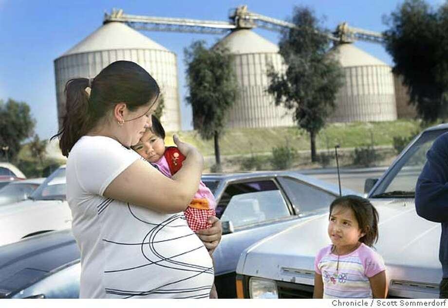 "INFANT PROJECT -- 93263  Leslie Gutierrez holds her little cousin ----XX---- while on a visit to her childhood home of Wasco in the shadows of the ---XX--- charcoal plant. Leslie feels that the nearby factories may have led to the deaths of her twin babies ""Socorro"" and ""Argelia"" (cq) who died on April 20th, 2002. SCOTT SOMMERDORF / The Chronicle Photo: SCOTT SOMMERDORF"