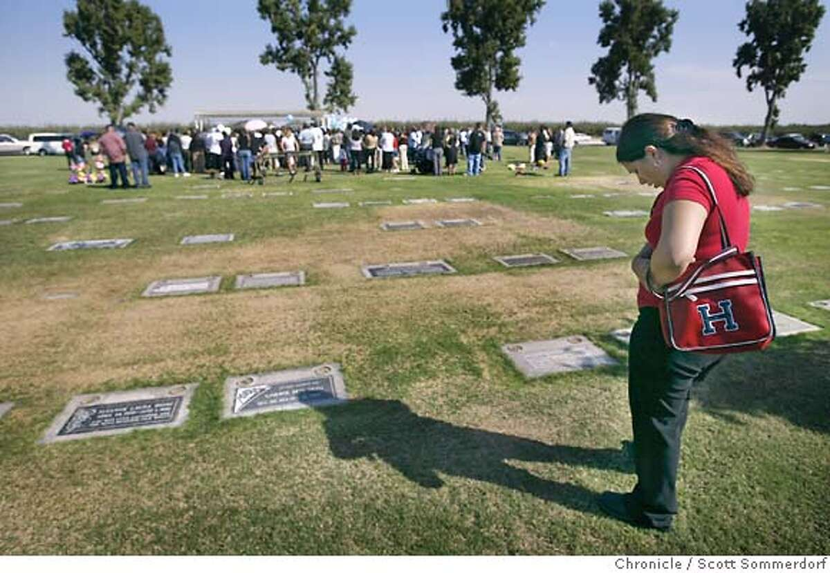 Leslie Gutierrez stands far away from the funeral service for 2 year-old Trinidad Trujillo.