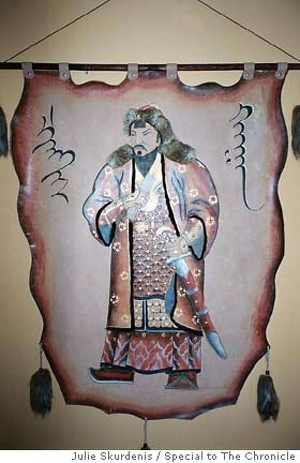 The image of Genghis Khan (better known in the Mongoliaas Chinggis) on leather hangs in an Ulan Batar restaurant. Photo by Julie Skurdenis, special to the Chronicle