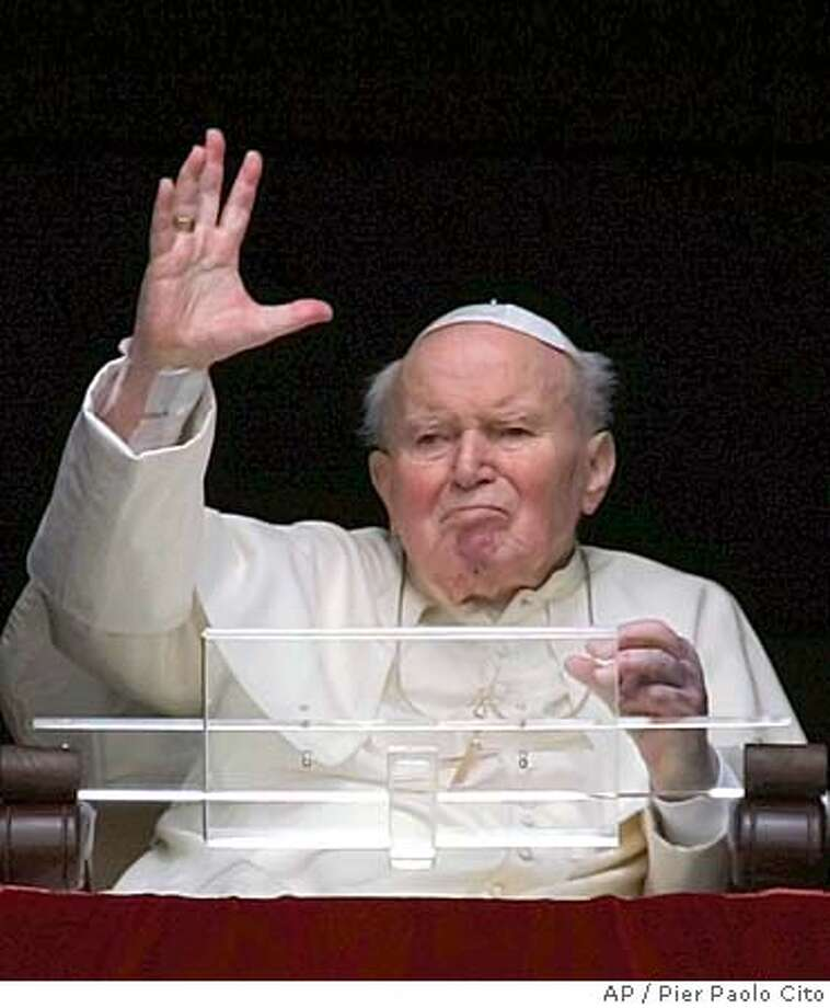 Pope John Paul II gives his blessing as he appears at the window of his studio overlooking St. Peter's Square at the Vatican, Wednesday, March 23, 2005. Looking gaunt, Pope John Paul II appeared at his studio window Wednesday and blessed faithful in St. Peter's Square. In the approximately one-minute-long appearance, the ailing pontiff raised his hand in blessing a few times but didn't speak. (AP Photo/Pier Paolo Cito) Photo: PIER PAOLO CITO
