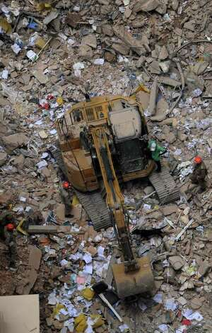 Firefighters and a sniffer dog work amid the rubble of the three collapsed buildings in downtown Rio de Janeiro, Brazil, on January.     AFP PHOTO/Vanderlei ALMEIDA Photo: VANDERLEI ALMEIDA, AFP/Getty Images / 2012 AFP