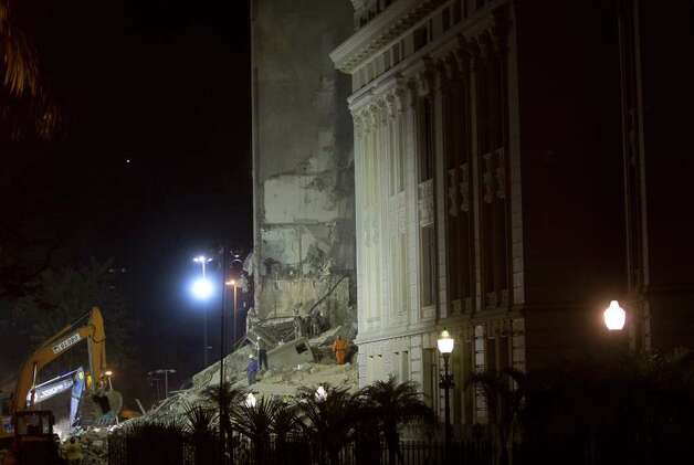 Firefighters search for survivors in a collapsed building in downtown Rio de Janeiro, Brazil, early Thursday. A multistory building collapsed in Rio's center Wednesday evening, leaving rubble strewn over a wide area. Photo: AP