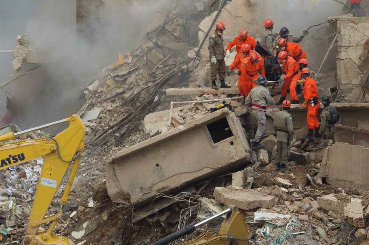 Rescue workers carry the body of a victim after a building collapsed in Rio de Janeiro, Brazil, Thursday Jan. 26, 2012. A multistory building collapsed in Rio's center Wednesday evening, leaving rubble strewn over a wide area but confusion about the number of possible victims and the cause.
