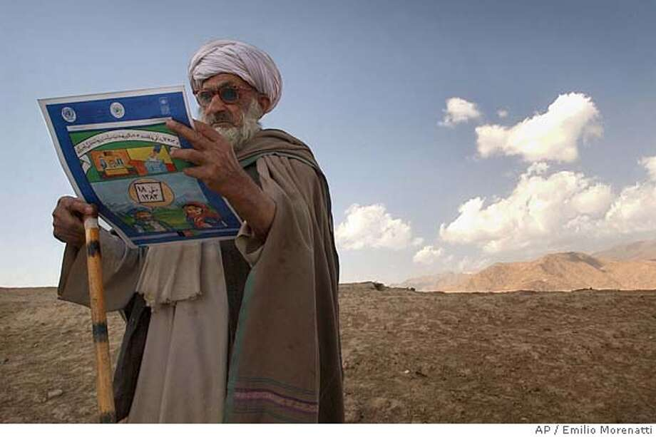 Kuchi tribesman Hediaul, 61, inspects a leaflet given to him which features sample of presidential election ballots and voting instructions sponsored by Afghanistan's joint electoral management body in Margareen village, about 20 kilometers (13 miles) east of Kabul, Afghanistan, Saturday, Oct. 2, 2004. Over 300 Afghan nomads of the Kuchi tribe gathered on a treeless hillside near a clutch of tents and mud-brick homes to learn from U.N. education officers how to take part in the Oct. 9 vote. (AP Photo/Emilio Morenatti) Photo: EMILIO MORENATTI