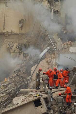 Rescue workers on Thursday carry the body of a victim after buildings collapsed in Rio de Janeiro, Brazil.Three bodies have been found, and 21 people are missing. Photo: AP