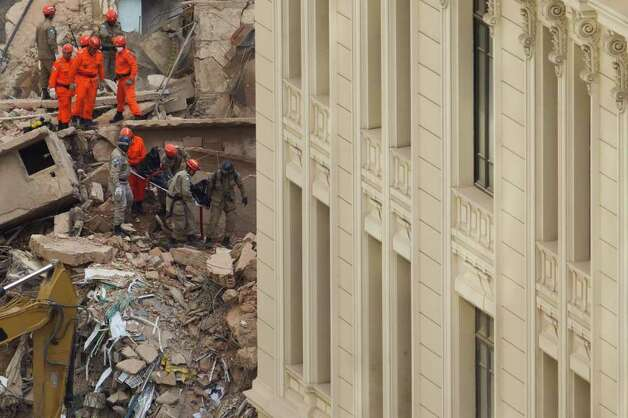 Rescue workers on Thursday carry the body of a victim after buildings collapsed in Rio de Janeiro, Brazil, on Thursday. Three bodies have been found, and 21 people are missing. Photo: AP