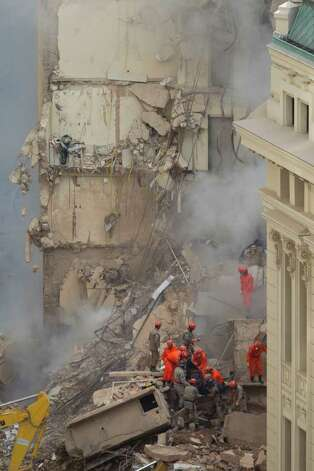 Rescue workers carry the body of a victim after buildings collapsed in Rio de Janeiro, Brazil, on Thursday. A multistory building collapsed in Rio's center Wednesday evening, leaving rubble strewn over a wide area. Photo: AP