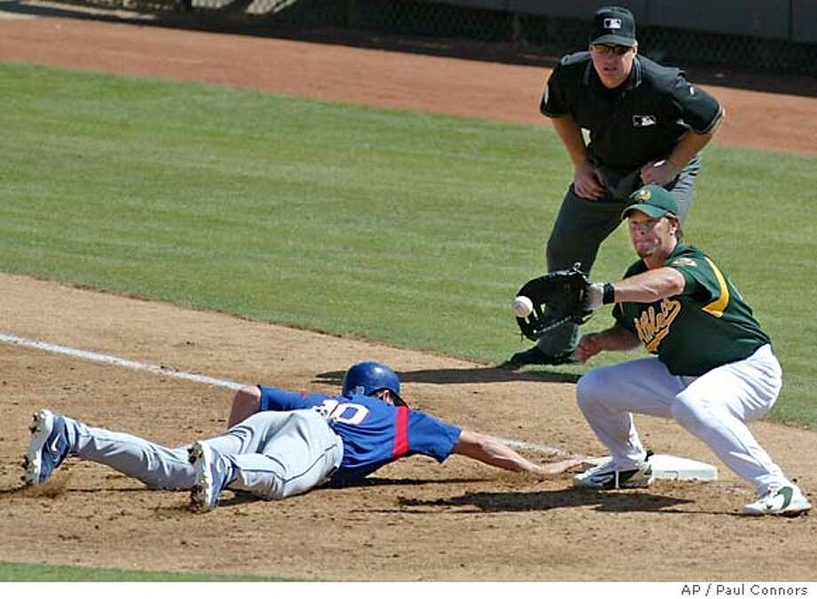 Texas Rangers ' Michael Young, left, dives safely back to the base as Oakland Athletics first baseman Scott Hatteberg, right, catches the throw and umpire Bill Miller, rear, makes the call in the second inning Wednesday, March 23, 2005, at Phoenix Municipal Stadium in Phoenix.(AP Photo/Paul Connors) Photo: ROBERT SCOTT BUTTON