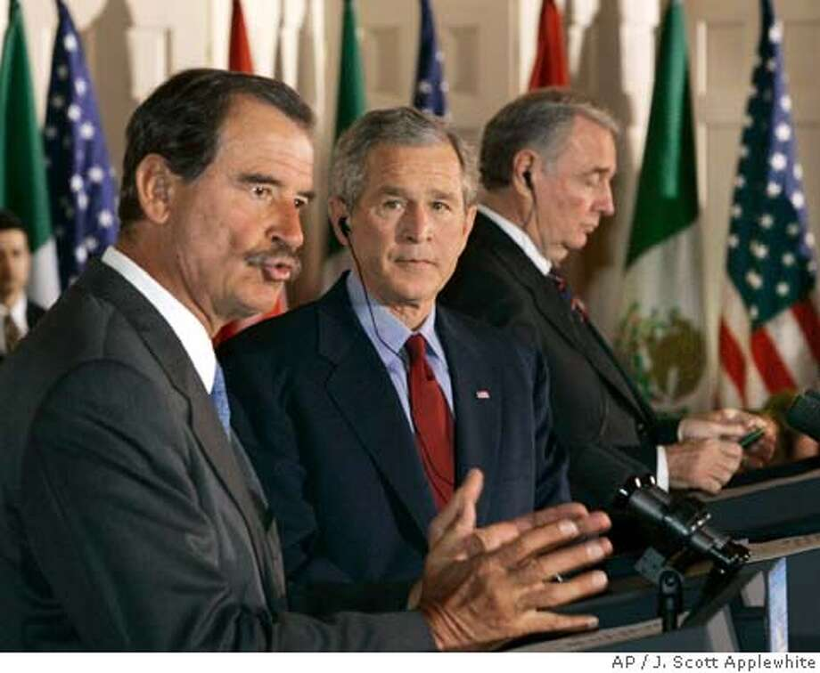 President George W. Bush, center, listens to remarks by Mexico's President Vicente Fox, left, with Canada's Prime Minister Paul Martin at right, during a joint news conference following their summit meeting at Baylor University in Waco, Texas, Wednesday, March 23, 2005. Relations have been strained between the U.S. and its closest neighbors and two biggest trading partners with trade, security and immigration issues as points of contention. (AP Photo/J. Scott Applewhite) Photo: J. SCOTT APPLEWHITE