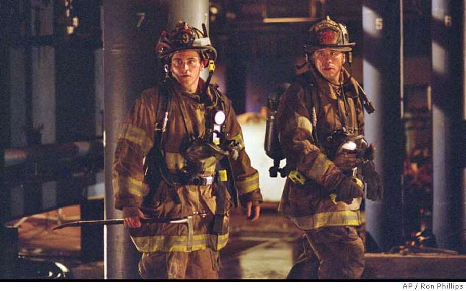 "Firefighter Jack Morrison (Joaquin Phoenix, left) and his mentor, Captain Mike Kennedy (John Travolta, right) team up to battle a life-threatening blaze in ""Ladder 49."" (AP Photo/Ron Phillips) Datebook#Datebook#Chronicle#10/01/2004#ALL#5star##0422376591 Photo: RON PHILLIPS"