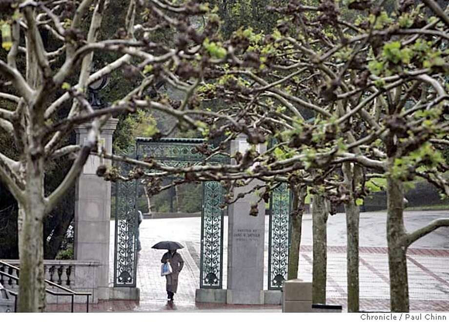 ucrain_013_pc.jpg  An umbrella-toting woman walks through Sather Gate at UC Berkeley on Tuesday. Rain continues to dampen the Bay Area and the Cal campus on 3/22/05 in Berkeley, CA.  PAUL CHINN/The Chronicle MANDATORY CREDIT FOR PHOTOG AND S.F. CHRONICLE/ - MAGS OUT Photo: PAUL CHINN