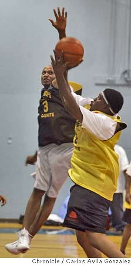 """Rob Holt, rear, tries to block a shot from """"Tank,"""" front, in the first game of the Late Night Basketball League in the Bayview/Hunter's Point neighborhood of San Francisco, Ca., on Wednesday, September 29, 2004. Yellow won the game, 65-63. Photo taken on 09/29/04, in San Francisco, Ca. Photo by Carlos Avila Gonzalez/The San Francisco Chronicle Photo: Carlos Avila Gonzalez"""