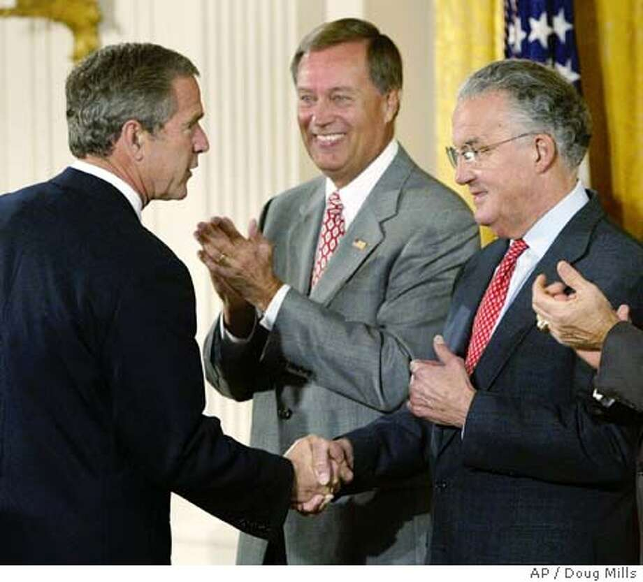 ** RETRANSMISSION TO CORRECT LEFT-TO-RIGHTS OF SARBANES AND OXLEY AND TO CORRECT SPELLING OF NAME OF ACT TO SARBANES-OXLEY NOT SABENS-OXLEY --ADVANCE FOR SUNDAY JULY 27 -- FILE ** President Bush shakes hands with Sen. Paul Sarbanes, D-Md, right, as Rep. Mike Oxley, R-Ohio, applaluds prior to signing the Sarbanes-Oxley Act in the East Room of the White House in Washington, Tuesday, July 30, 2002. The law aims to make financial information released by public companies as accurate as possible by tweaking the checks and balances already in place. It boosts the independence of corporate boards and auditors and threatens serious sanctions for chief executives and chief financial officers who violate the rules. (AP Photo/Doug Mills) CAT 162 dpi Photo: DOUG MILLS