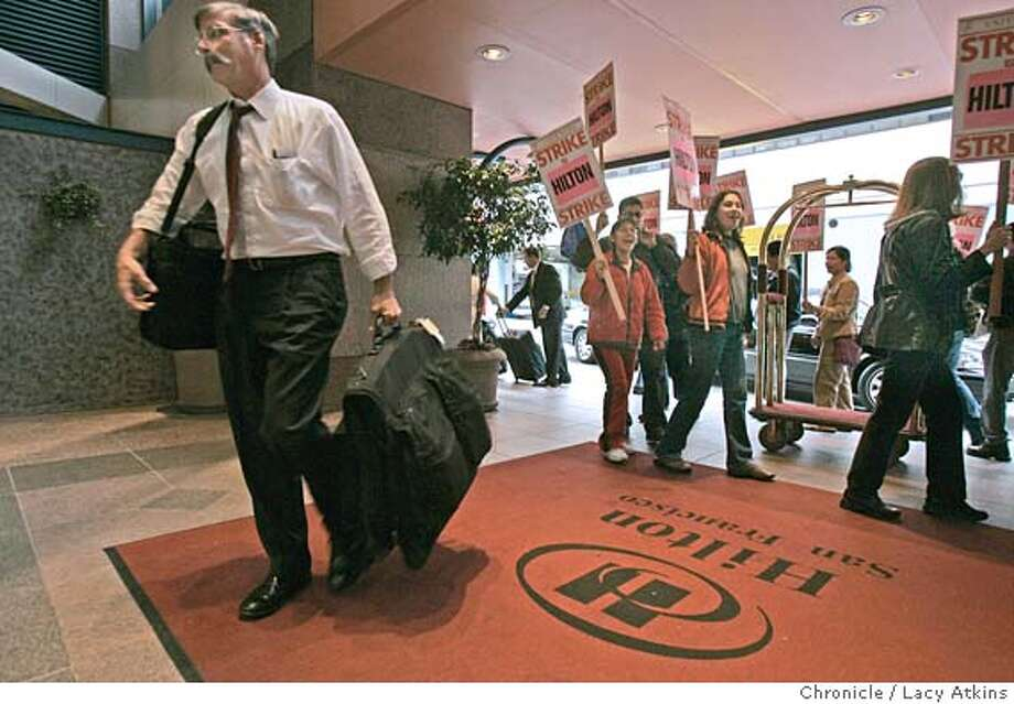 Customers still chech in at the Hilton Hotel as protesters from Local Union 2 hotel workers march the the doors claiming ongoing unfair labor practices, in San Francisco, Sept.29, 2004. The Person with the suitcase, checking in, declined to give his name.  LACY ATKINS/ The Chronicle MANDATORY CREDIT FOR PHOTOG AND SF CHRONICLE/ -MAGS OUT Metro#MainNews#Chronicle#9/30/2004#ALL#5star##0422383388 Photo: LACY ATKINS