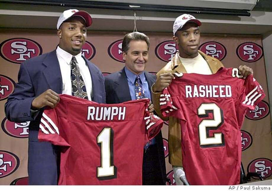 San Francisco 49ers top draft picks Mike Rumph, left, a cornerback from Miami, and Saleem Rasheed, right, a linebacker from Alabama, pose with 49ers coach Steve Mariucci during a news conference in Santa Clara, Calif., Sunday, April 21, 2002. (AP Photo/Paul Sakuma) ALSO RAN 07/24/02 CAT DIGITAL IMAGE Sports#Sports#Chronicle#9/30/2004#ALL#5star##421880368 Photo: PAUL SAKUMA