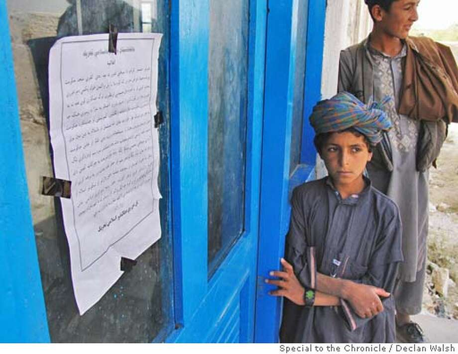 Afghan men land boys with a 'night letter' pinned ot the door of the town mosque in Uruzgan town, Uruzgan province, central Afghanistan. September 04. By Declan Walsh Photo: Declan Walsh