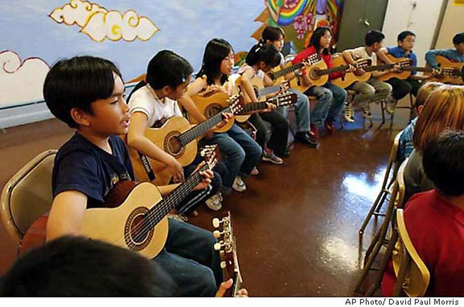 Kids who are in the Little Kids Rock program entertain and are entertained by Bonnie Raitt, Tom Waits, Norton Buffalo, Jason Newsted and Justin Willacy on October 21, 2003 at the Spring Valley Elementary School in downtown San Francisco . (AP Photo/ David Paul Morris) Photo: David Paul Morris