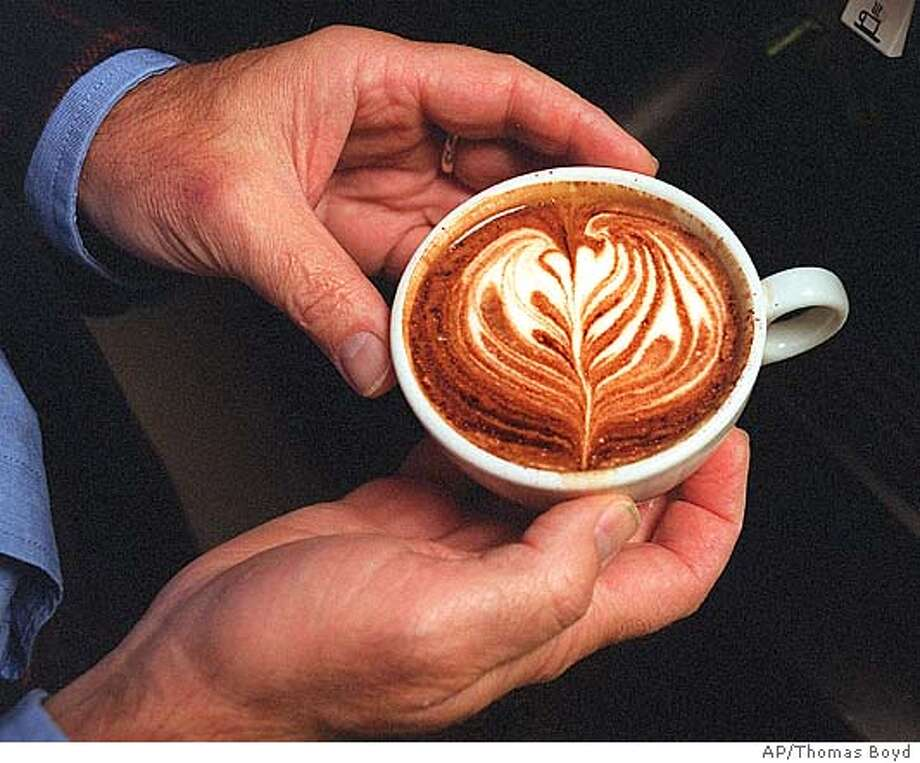 ADVANCE FOR MONDAY DEC. 31--Bruce Milletto's coffee consulting company, Bellissimo Coffee Infogroup, makes videos that detail how to make the perfect espresso and other drinks such as this one seen here Tuesday, Nov. 20, 2001, in Eugene, Ore. (AP Photo/The Register-Guard, Thomas Boyd) Photo: THOMAS BOYD