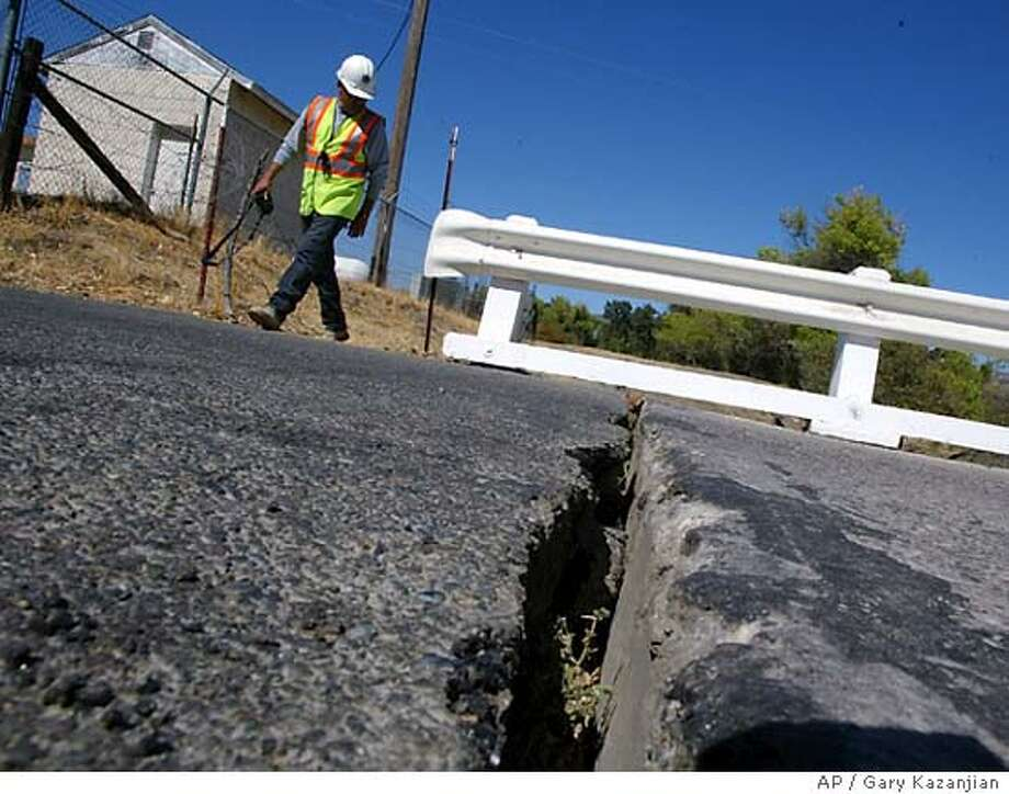 Ramon Martinez of Monterey Co. Public Works checks a crack in a bridge from an earthquake Tuesday, Sep. 28, 2004 in Parkfield, Calif. The bridge suffered some strutural damage including separating nearly six inches from the road. (AP Photo/Gary Kazanjian) Photo: GARY KAZANJIAN