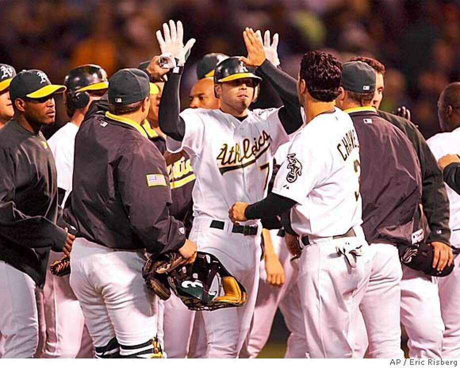Oakland Athletics' Bobby Crosby, center, is greeted by Eric Chavez and his teammates after hitting a game-winning sacrifice fly in the ninth inning against the Seattle Marinersof their game in Oakland, Calif., Monday Sept. 27, 2004. The A's won the game, 6-5.(AP Photo/Eric Risberg) Sports#Sports#Chronicle#9/28/2004#ALL#5star##0422377725 Photo: ERIC RISBERG