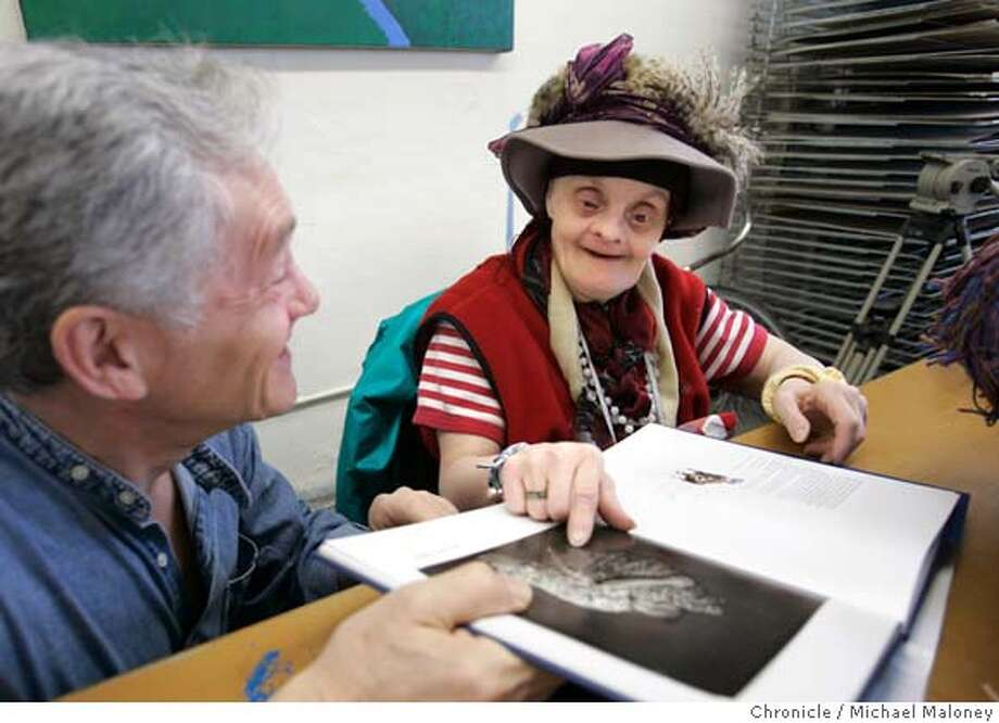 "ARTISTS_047_MJM.jpg  Photographer Leon Borensztein (left) shows artist Judith Scott a portrait he took of her and published in a book. It was the first time she saw the image.  Leon Borensztein is an Oakland photographer whose current show at Yerba Buent Center for Arts and book, ""One is Superman, One is Adam,"" reveal the inner lives of developmentally disabled artists that he has been photographing at the Creative Growth Art Center in Oakland for more than a decade. Some are able to communicate well, others are profoundly disabled, but all of them create works that are at once vibrant, inspiring and deeply reflective of society's unease with those who do not ""look"" like the narrow norm. Photo by Michael Maloney / San Francisco Chronicle MANDATORY CREDIT FOR PHOTOG AND SF CHRONICLE/ -MAGS OUT Photo: Michael Maloney"