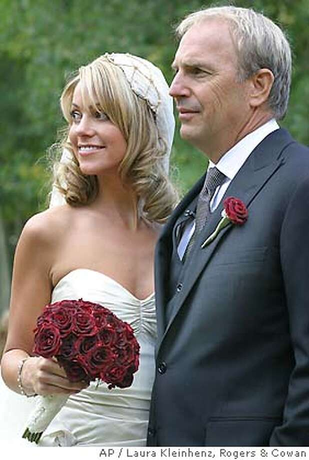 Actor Kevin Costner, right, 49, and his bride Christine Baumgartner, 30, pose for a photograph at their wedding, Saturday, Sept. 25, 2004, at the actors residence in Aspen, Colo. The couple were wed in a private afternoon ceremony before 300 close friends and family. This is the second marriage for Costner and the first for Baumgartner. (AP Photo/Rogers & Cowan, Laura Kleinhenz) Photo: LAURA KLEINHENZ