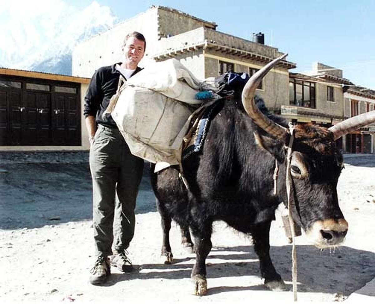 John Wood delivering books on the back of a yak, Annapurna Range, Nepal, 2002.