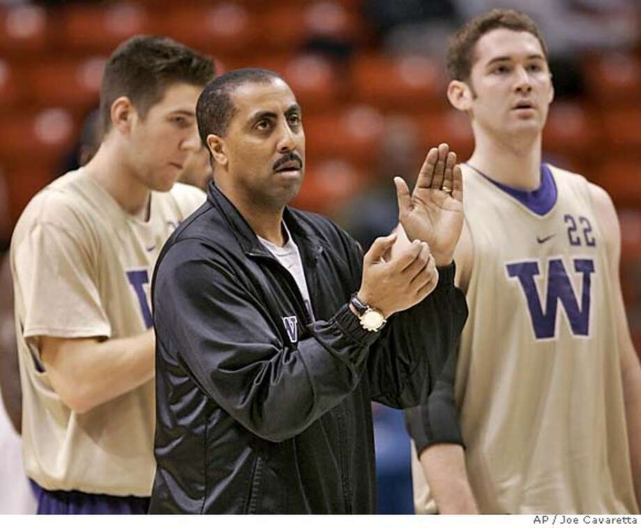 Washington head coach Lorenzo Romar, center, stands with players Hans Gasser, right, and Matt Fletcher during team practice for the first round of the NCAA Tournament in Boise, Idaho, Wednesday, March 16, 2005. Washington is scheduled to play Montana on Thursday. (AP Photo/Joe Cavaretta) Photo: JOE CAVARETTA