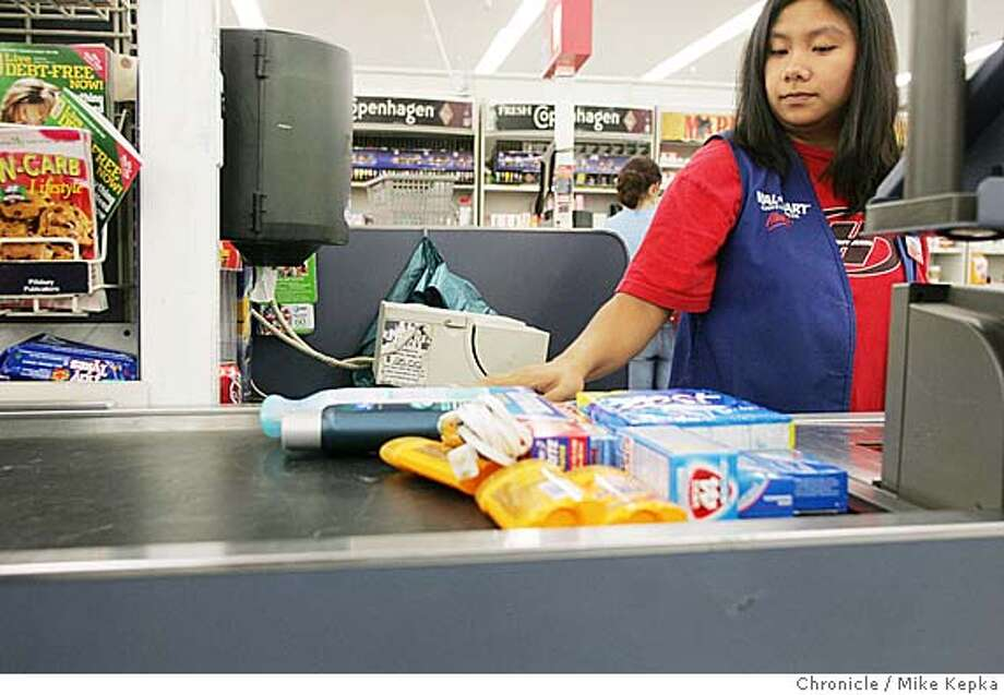 walmart0077_mk.jpg Sonia Chantioco, Walmart employee for 1 yr 3 months, checks customers out.  Walmart lets the Chronicle inside its doors in an effort to tell their side of a long line of labor disputes.  MIKE KEPKA/The Chronicle MANADATORY CREDIT FOR PHOTOG AND SF CHRONICLE/ -MAGS OUT Business#Business#Chronicle#9/24/2004#ALL#5star##0422370707 Photo: MIKE KEPKA